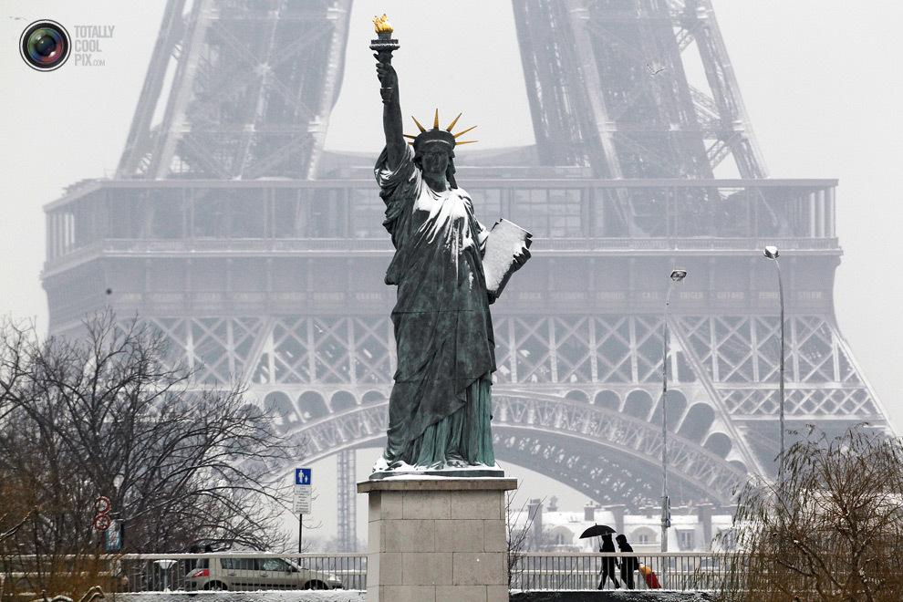 Снег заметает копию американской статуи Свободы возле Эйфелевой башни.